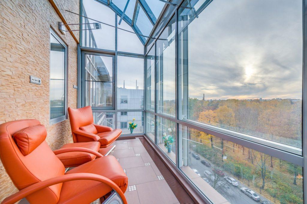 Панорамное остекление балкона с красными креслами